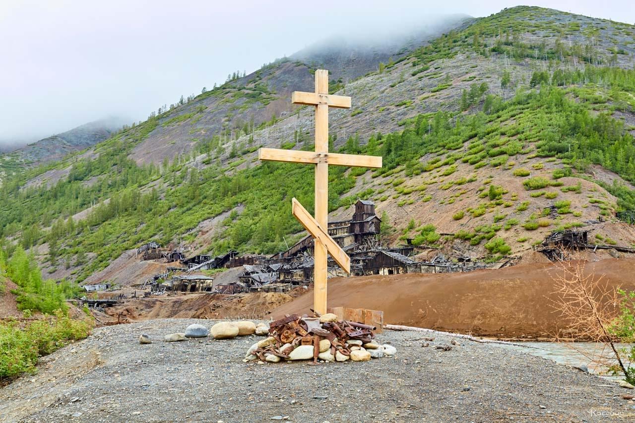 Памятный крест на берегу реки Сеймчан. На заднем плане фабрика №3 имени Чапаева.