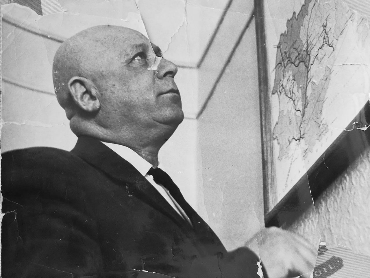 Абрам Исакович Геренштейн у карты дорог Магаданской области.