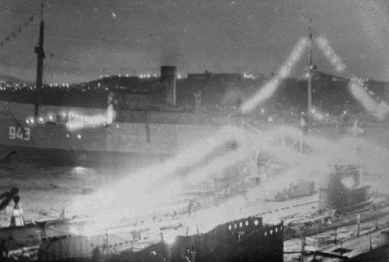 Праздник в бригаде. Флаги расцвечивания и огни говорят о то, что это значимый день. На фото видна плавбаза «Север».