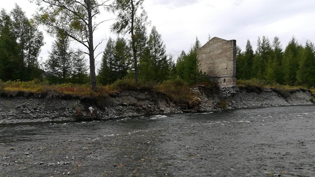 Уцелевшая каменная стена здания.