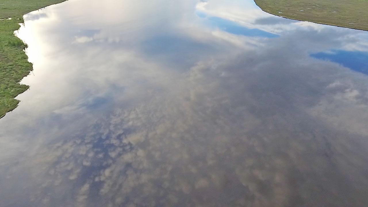 Отражение белоснежных облаков на синем небе и спокойствие воды на озере.