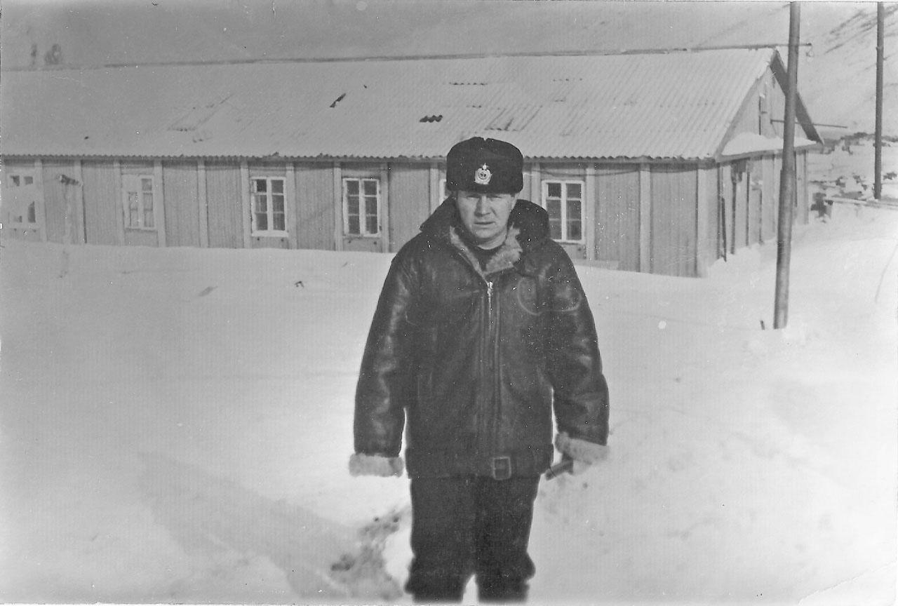 Остров Симушир. Баталер, мичман Потапов Виталий Павлович. За ним видна казарма-клуб, в которой мы жили на острове.