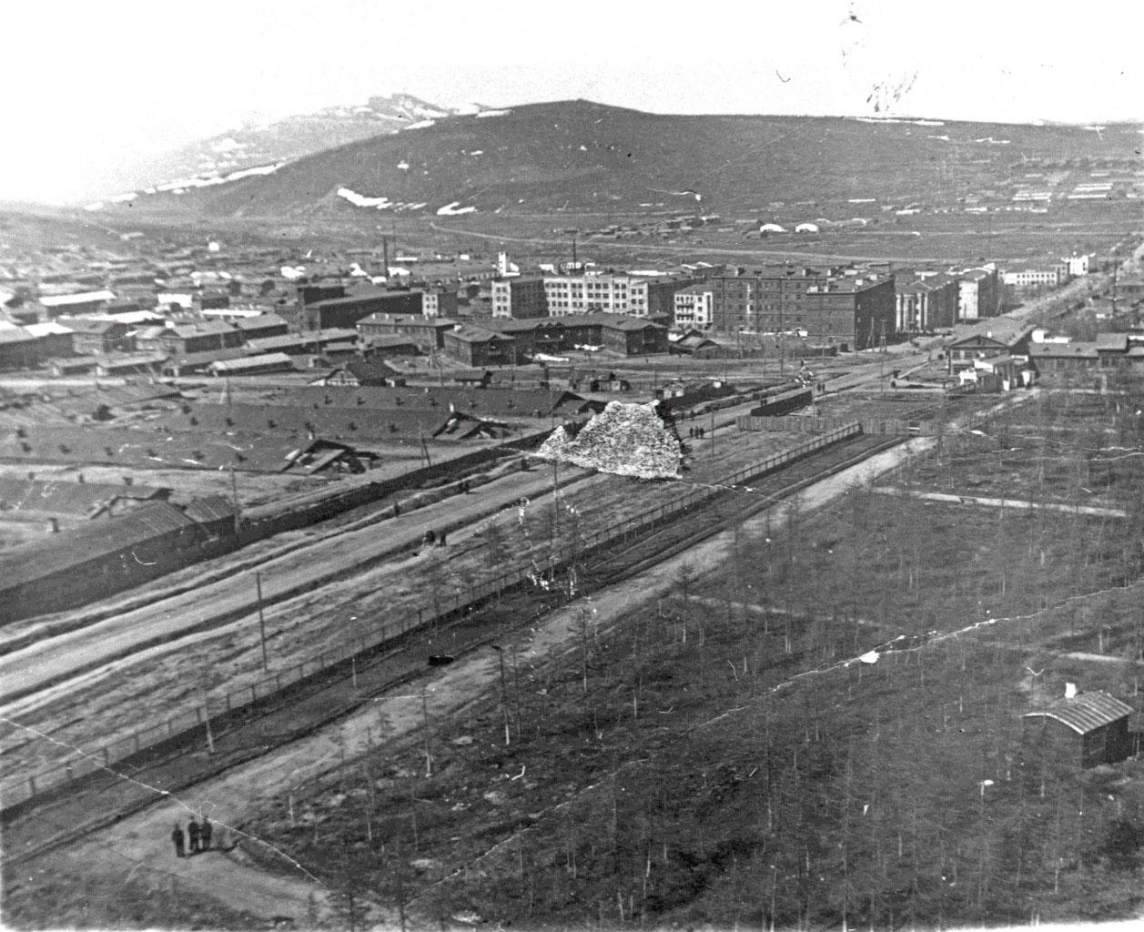 Перспектива Колымского шоссе (ныне пр. Ленина) от сангородка к мосту через р. Магаданку и далее, вглубь материка. Фото сделано в 1941 году с установленной в парке парашютной вышки.