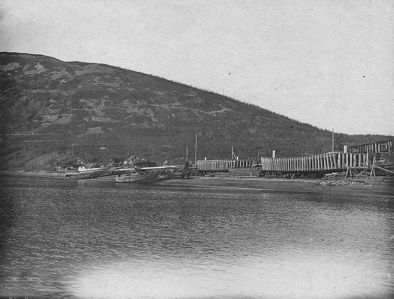 Аэродром в бухте Нагаево. На берегу строящиеся кунгасы и баржи морского типа. У берега - летающая лодка «Dorner-Wal» Н-1. 1933 год